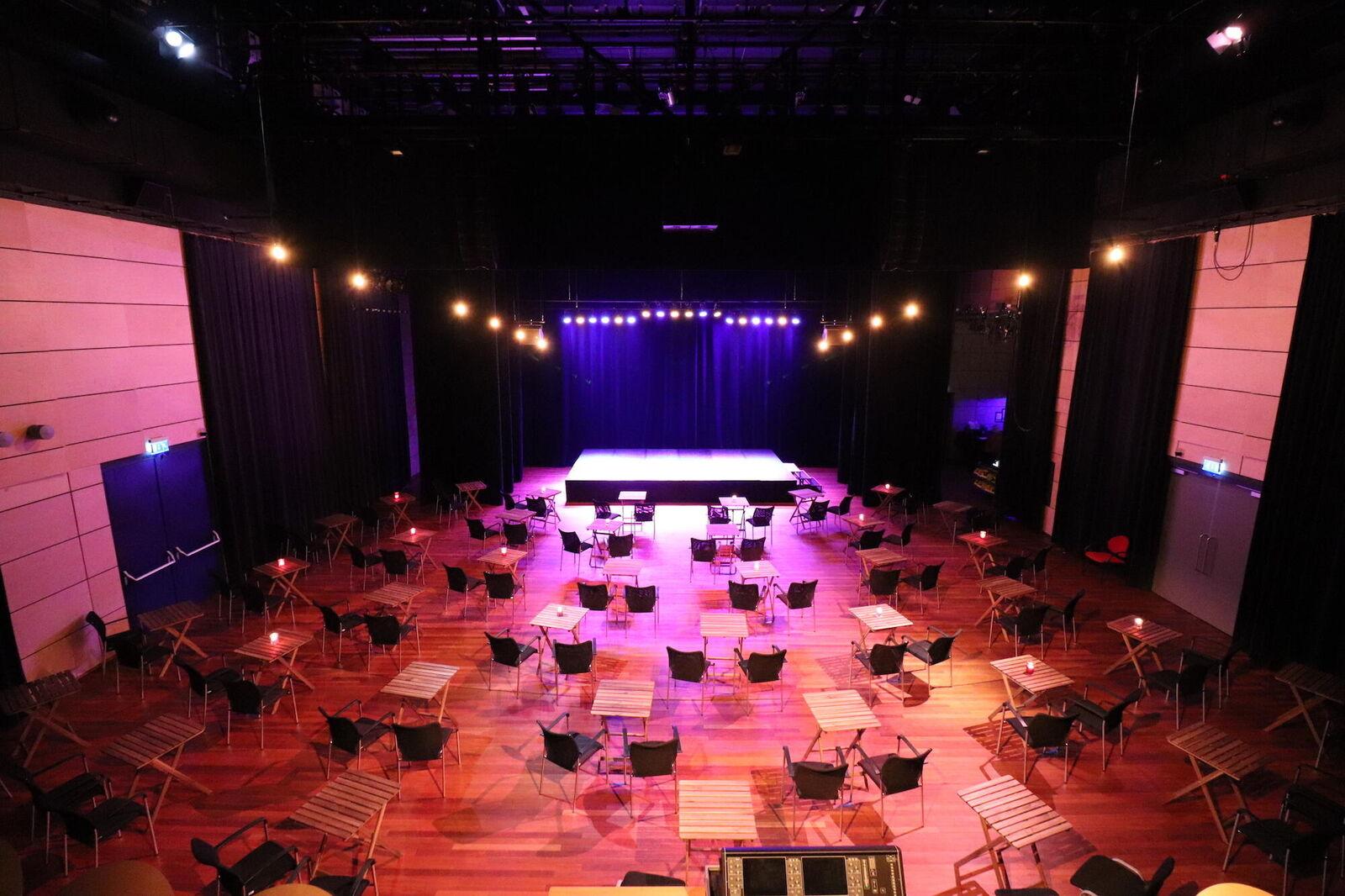Gezellige setting in Theaterzaal met tafeltjes en stoeltjes